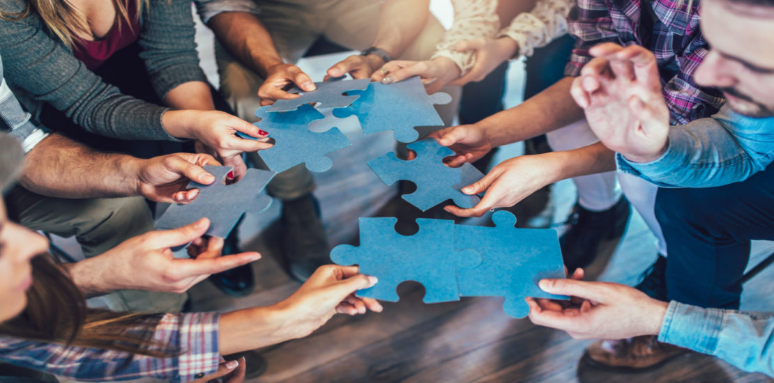 Businesspeople joining puzzle pieces in office, close up.